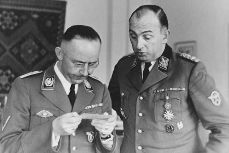 The Banality of Evil: Heinrich Himmler (committed suicide) and Kurt Daluege (hanged for war crimes), at Hegewald bei Zhitomir, Himmler's headquarters in the Ukraine. Located on a former Soviet airbase between Zhitomir and Vinnitsa on the Teteriv and Gryva Rivers, the Hegewald compound was run by over 100 SS officers and 1,000 SS police. It contained an airport, cemetery, bunkers, banquet rooms, elegant houses, and an office and private quarters. It was used between July 24, 1942 and the…
