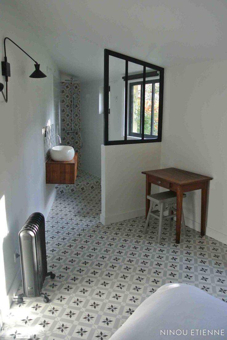 Voilà une jolie salle de bains à la forme atypique ! On adore son sol en en carreaux de ciment et sa verrière d'intérieur...