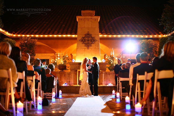 A outdoor night wedding ceremony with multi-colored candles lighting the aisle   villasiena.cc