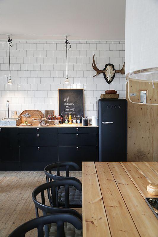 Tænker: sort køkken - hvide fliser - træ på gulv, loft og plankebord og bænken under vinduet....NB! læg mærke til fed dør af birkefiner?