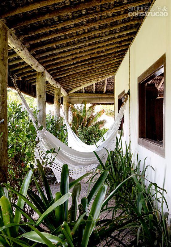 Janelas amplas e cobertura natural integram bangalô à paisagem - Casa