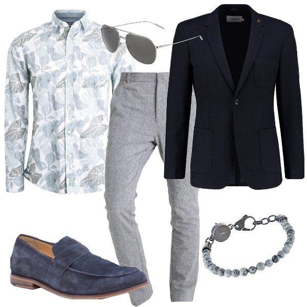 I pantaloni grigi picchiettati hanno la gamba stretta e l'orlo regolare. Sono abbinati alla camicia leggera bianca con fantasia grigio chiaro a maniche lunghe e collo alla francese e alla giacca blu scuro dal taglio slim chiusa da un solo bottone. Ai piedi mocassini in camoscio blu da portare senza calzini. Per finire occhiali con montatura in metallo argento con lenti grigio scuro e bracciale di perline grigie e gancio argento.