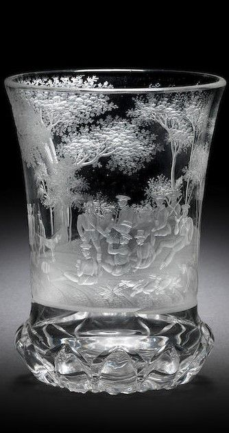 A Bohemian engraved Ranftbecher by Franz Hansel, Rodowitz, circa 1830 The flared cylindrical form finely decorated with a continuous woodland scene comprising a group of huntsmen and their dogs at leisure on a hillock, sitting drinking, smoking and enjoying themselves, the birds and hare from the hunt lying on the ground beside them, the reverse with a small pond, the foot with a band of deeply cut gadroons and the base cut with hobnail diaper, 13.9cm high