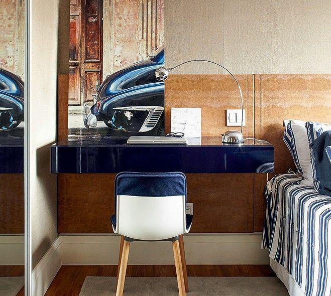 Neste quarto, o arquiteto Nelson Kabarite aproveitou o espaço em uma das laterais da cama para montar o cantinho de trabalho do morador. Entre os tons escolhidos, o azul se destaque e traz personalidade à escrivaninha