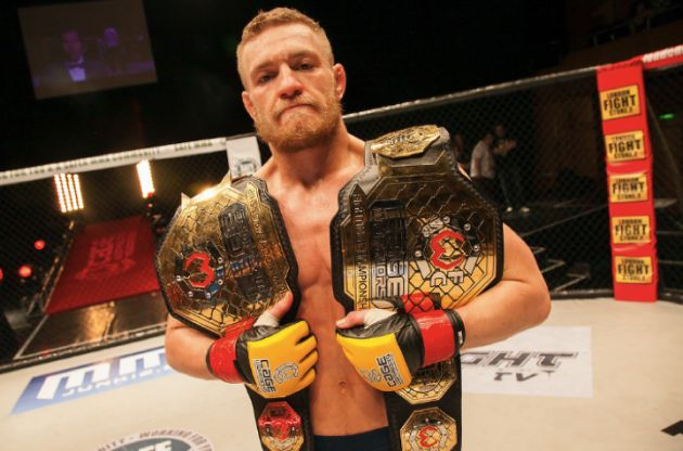 Conor McGregor with the Cage Warriors featherweight and lightweight belts.