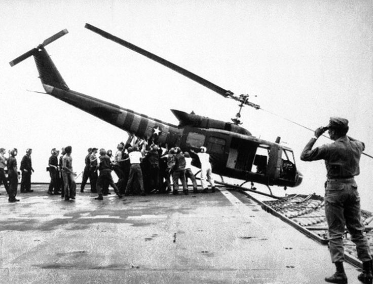 April 29, 1975- U.S. Navy personnel aboard the USS Blue Ridge push a helicopter into the sea off the coast of Vietnam in order to make room for more evacuation flights from Saigon.
