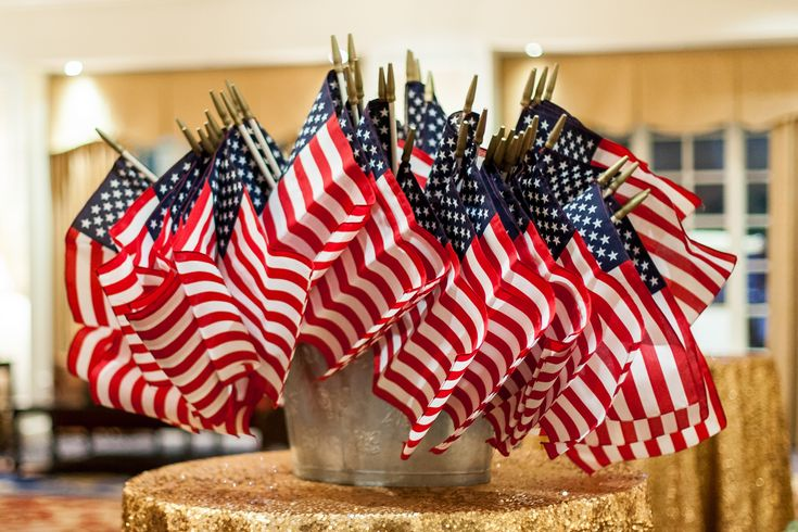 Since the groom is a Captain in the United States Marine Corps, loved ones took miniature American flags from a display on a gold sequin table to prepare for the couple's flag waving reception exit. #weddingfavors Photography: Renee Sprink Photography. Read More: http://www.insideweddings.com/weddings/a-blue-white-gold-military-wedding-at-duke-university-chapel/622/