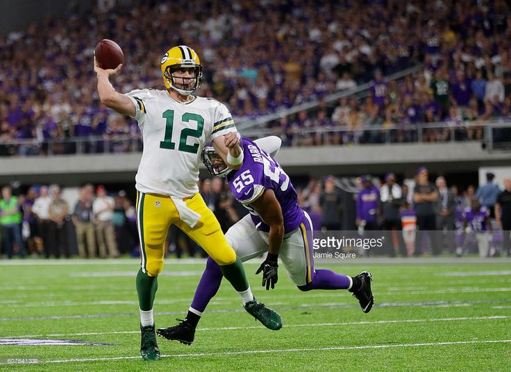 Aaron Rodgers #12 of the Green Bay Packers passes the ball while being pursued by defender Anthony Barr #55 of the Minnesota Vikings during their game on September 18, 2016 at US Bank Stadium in Minneapolis, Minnesota.