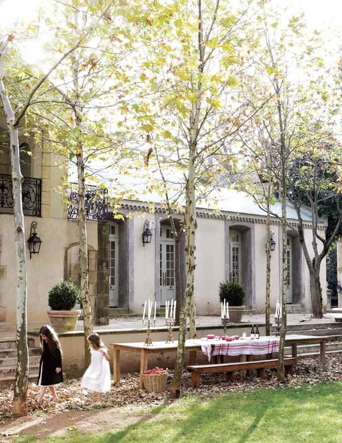 The homeowners' daughters play among the plane trees that frame an alfresco dining area. The bronze Napoleon III candelabra on the table are from the Clignancourt in Paris.