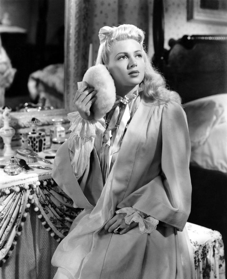 Lana Turner in dressing gown and with a giant powder puff. Vanity Table. Classic Hollywood glamour.