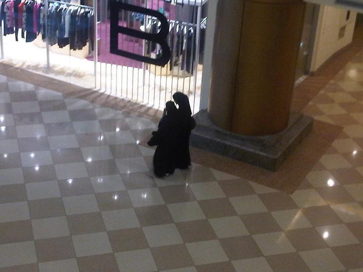 #arabiasaudita È lì che, specialmente verso sera, le ragazze nelle loro abaya e dietro i loro niqab vanno avanti e indietro per i corridoi di marmo e sulle scale mobili come in una lunga gabbia ad aria condizionata. Le unghie laccate, la matita calcata sugli occhi, la borsa e gli occhiali scuri dai marchi bene in vista: tutto ciò che emerge dalla loro divisa viene messo in risalto. Sono i segnali di ciò che non possono dire in altri modi.