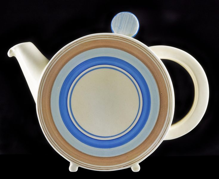Teapot and cover, cream earthenware painted in dark blue, pale blue and brown with concentric bands and lines: English, Staffordshire, Burslem, by Newport Pottery Co. Ltd, designed by Clarice Cliff, c. 1935