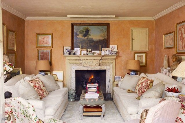 The small perfectly formed sitting room in the designer Nicky Haslam's country house is the ideal cosy space. The low Victorian bench takes the place of a coffee table. This soft colour on the walls gives a complexion-flattering glow, especially if the buff card-shaded lamps are lit. Use subdued light upwards, but bright pools below for reading. The sofas are slip-covered in a hard-wearing off­-white cotton.