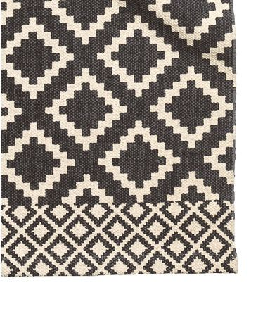 Gebroken wit/zwart. Een rechthoekig vloerkleed van geweven katoen met een geprint dessin op de bovenkant.