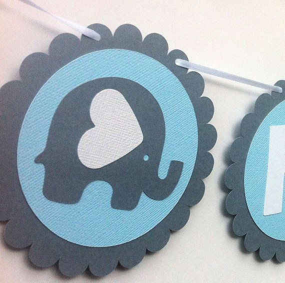 Blue, gray and white garland made from scalloped circles, each with a textured cardstock disc and the text BABY BOY in white. Three elephant
