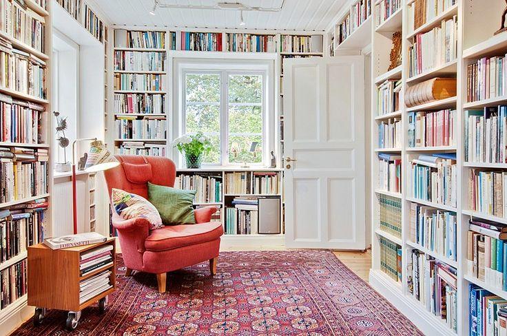Läshörna i vardagsrummet med vackra detaljer som platsbyggda bokhyllor och takpanel