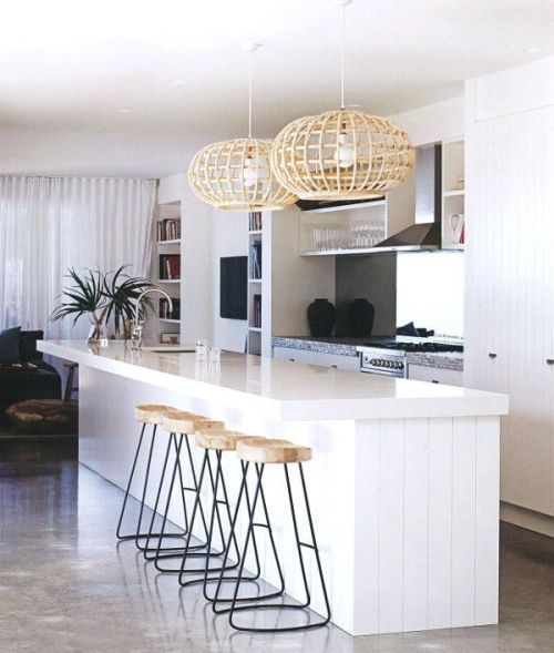 Modern, coastal kitchen with metal base, wood topped bar stools and a pair of unique pendant lights