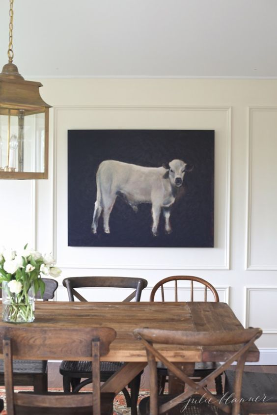 Farmhouse table & mix of dining chairs.  vintage pendant & Cow Portrait