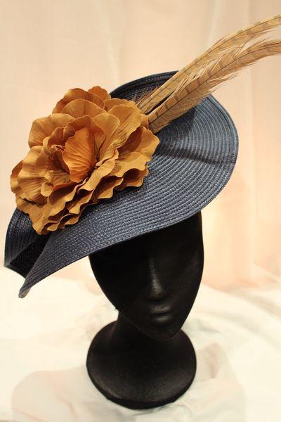 Elegante tocado con forma de ala de pamela.  Consta de un plato en color azul adornadoconplumas de faisan y flon en  tonos ocres.   Ideal para resa...