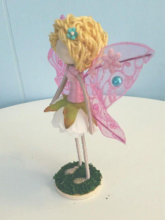 Esta hada 5 pulgadas de alto y tiene pelo rubio rizado, una blusa rosa y una falda de flor blanca, con alas de color rosa brillantes. Ella se encuentra en una base de 1,5 pulgadas cubierto de césped verde. Viene en una caja de regalo blanca.