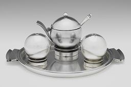 Condiment Set: Mustard Pot [Designers: Georg Jensen and Harald Nielsen; Date: 1927; Origin: Denmark; Material: Silver]Designed by Scandinavians, this condiment set has strong influences of Japanese design, but still adheres to the changes in aesthetic towards machine aesthetic at the turn of the century. These pots were manufactured to display the strong spherical geometric shape.