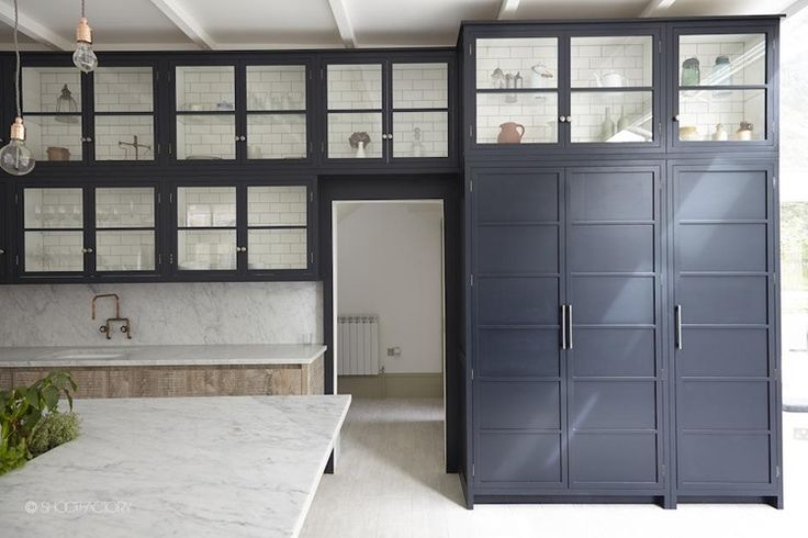 Black upper cabinets and pantry, bleached lower cabinets, marble backsplash and countertops, light floor.