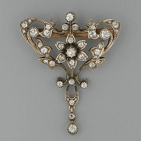 An Edwardian diamond brooch Of open floral cartouche design, silver and gold set with old brilliant-cut diamond