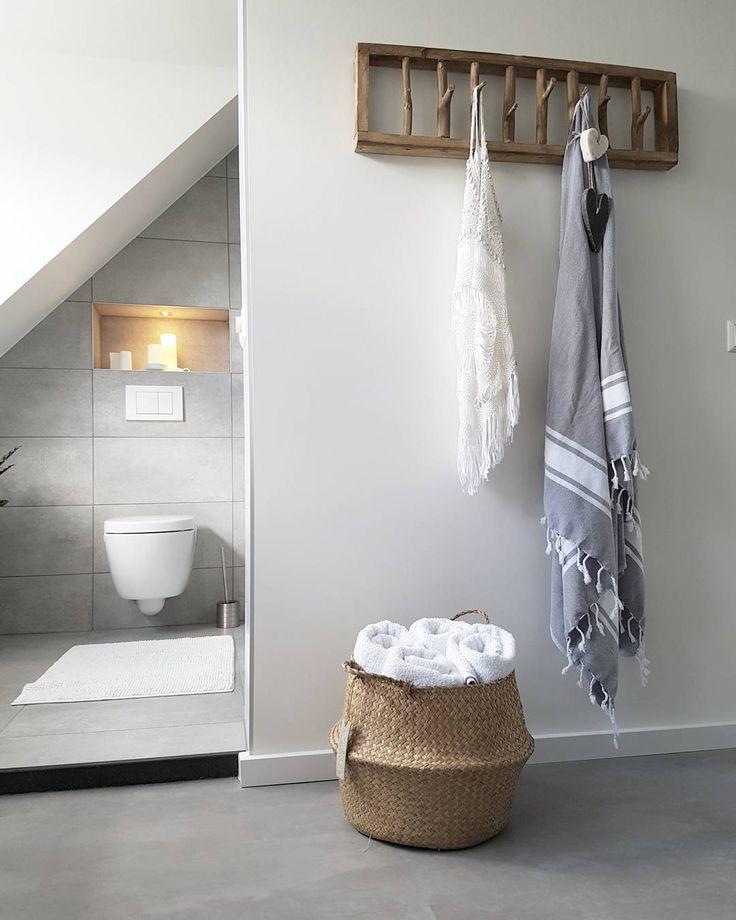 Lichte scandinavische badkamer met wit en grijs tinten, aangevuld met natuurlijke materialen voor een warme sfeer.