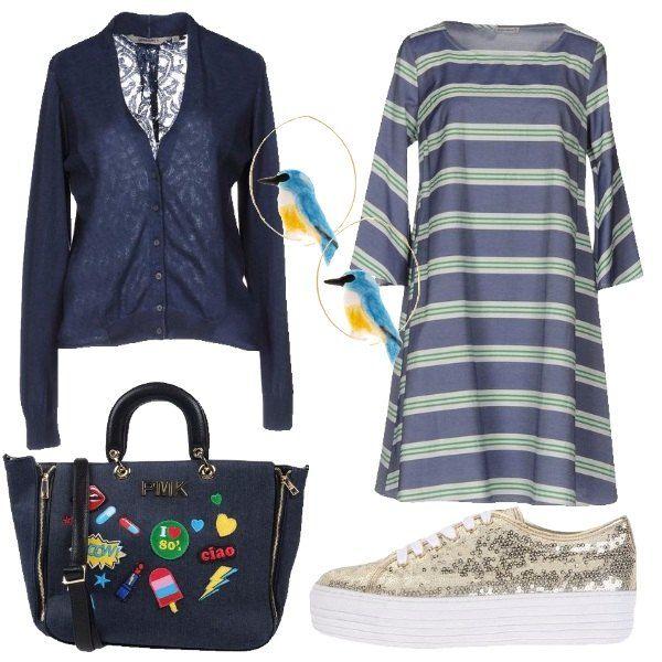 Il vestito a trapezio blu con le maniche 3/4 è in un tessuto fresco di cotone a fantasia di righe orizzontali bianche e verdi. Lo abbiniamo al cardigan blu in cotone con la schiena in pizzo tono su tono. Ai piedi sneakers ricoperte di paillettes oro e para bianca alta e come borsa una shopping bag blu color jeans con patches in vari colori e manico e tracolla neri. Per finire orecchini a cerchio dorati con decoro di uccellino blu e giallo su entrambi.