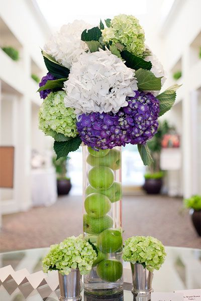 A fruit-filled vase punches up this tall hydrangea arrangement. Photo by: Captured Photography
