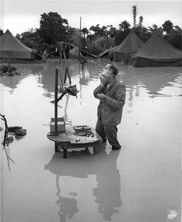 US Marine Staff Sergeant A S. Barnacle shaving in his camp on Okinawa Japan ignoring the heavy flooding due to rain 28 May 1945.