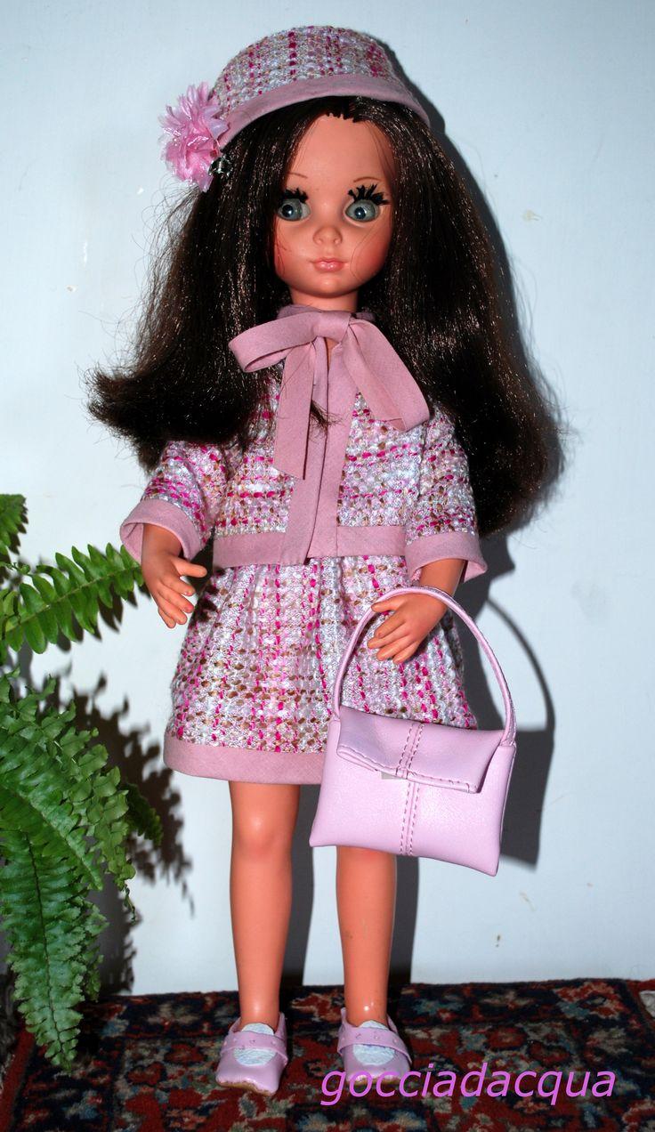Susanna in un tailleur rosa bon ton liberamente ispirato a 'Cordobes' 1968, accessoriato con cappellino coordinato e scarpe e borsa in tinta