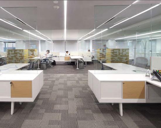 La iluminación clara y uniforme complementa la espléndida luz natural que entra a través de los grandes ventanales. Los tapetes en distintos tonos de gris marcan la diferencia funcional de los espacios, mientras que una moderna silla en tapizado amarillo invita a la concentración.