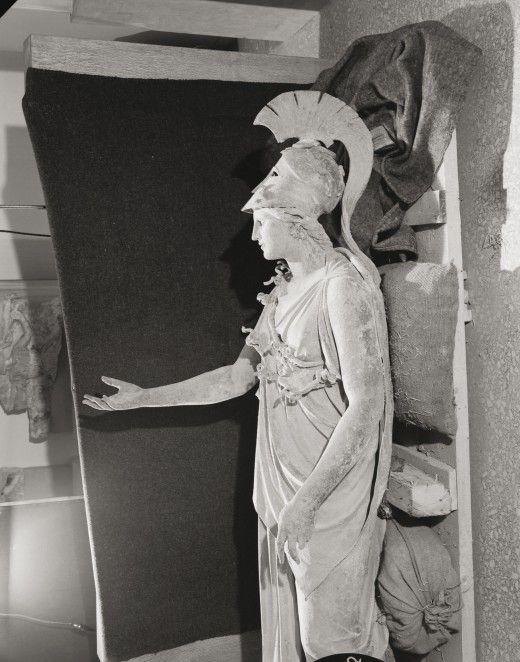 O φωτογράφος Δημήτριος Χαρισιάδης φωτογραφίζει τους Χάλκινους Θεούς του Πειραιά αμέσως μετά την ανασκαφή τους στη διασταύρωση των οδών Γεωργίου Α' και Φίλωνος στον Πειραιά. Ιούλιος 1959  © Φωτογραφικό Αρχείο Μουσείου Μπενάκη