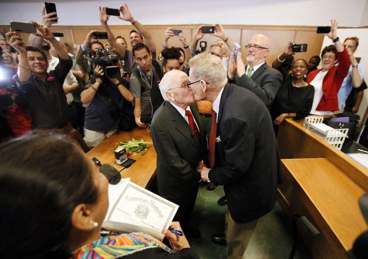 Dallas, Texas, Stati Uniti -  Il giudice Dennise Garcia, di spalle, guarda George Harris, 82 anni, e Jack Evans, 85 anni, che si baciano dopo essere stati sposati a Dallas, il 26 giugno 2015. I due uomini sono stati la prima coppia a essersi sposata nella contea di Dallas, in Texas, dopo la storica decisione della Corte Suprema che ha dichiarato incostituzionali i divieti ai matrimoni gay in tutti gli stati americani. Harris e Evans stanno insieme da 54 anni. - Il Post