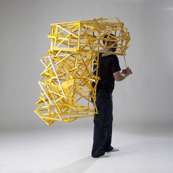 L'artiste Tracy Featherstone imagine des sculptures portables faites de pièces de bois.    Entre architecture, mobilier et vêtement, ces structures s'enfilent et se portent, la matière affrontant la chair, épousant les courbes et les contraignant à la fois.