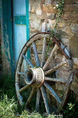 chippy blue wagon wheel leaning against stone wall