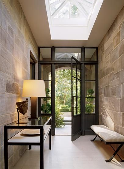 very simple & beautiful entrance .. brick walls, iron glass console table and bench.