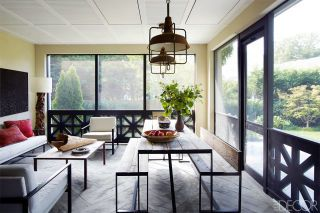 When it came to the decor, the homeowners and designer were in sync, favoring clean-lined furniture—like the ebonized-oak dining table and 1950s leather sling chairs—but avoiding extraneous flourishes such as window treatments. The carefully chosen accessories include a Burmese bronze chain suspended from a living room wall and an enormous antique Spanish olive jar in the master bedroom. A pair of Art Deco–era industrial lights hangs above a custom-made table and benches in the screened…