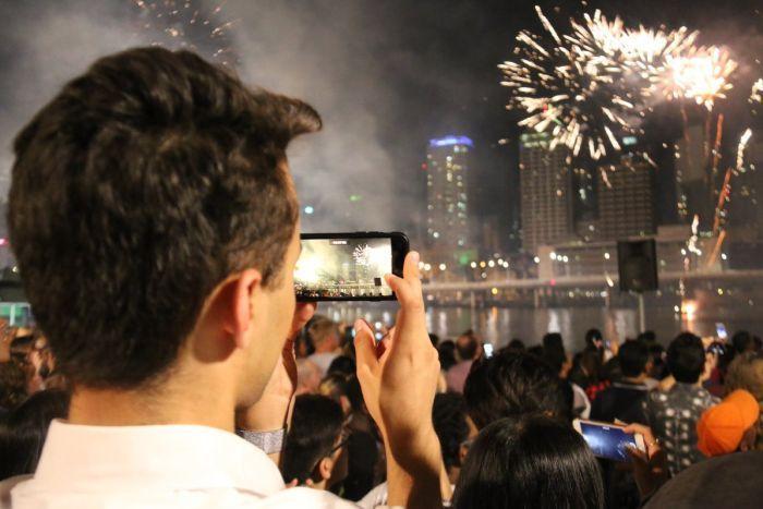 A reveller watches fireworks in Brisbane