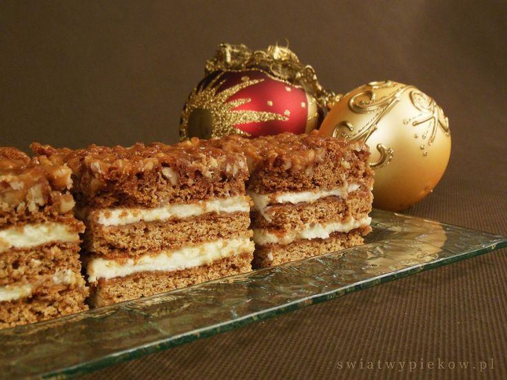 Pyszne miodowe ciasto, przełożone dżemem śliwkowym i budyniowym kremem, polane orzechowym karmelem. Idealny wypiek na świąteczny stół.