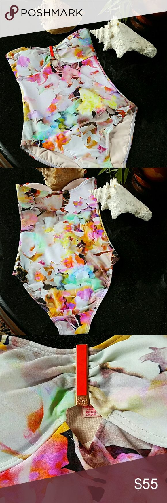 Ted Baker Swim NWOT FEATURES: Women's one-piece swimsuit Bandeau neckline Cut out detail to front Lightly moulded, wired cups Allover watercolour floral print Hand wash MATERIAL: Shell: 80% Polyamide, 20% Elastane; Lining: 100% Polyester Exude demure chic in this Belah swimsuit from Ted Baker. Moulded, wired cups flatter and support while an allover floral print supplies feminine detail. Wear yours with an oversized hat and sunglasses. Labels may be snipped or marked. Ted Baker Swim One…