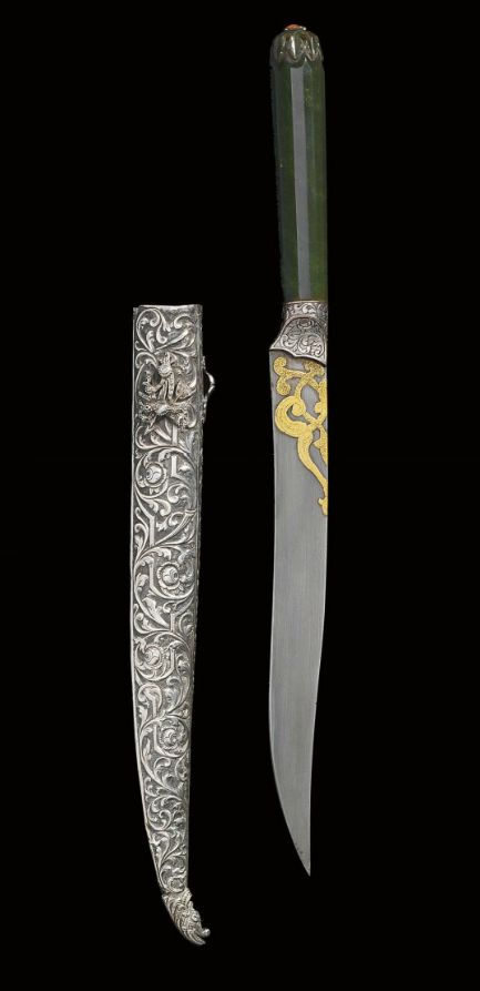 AN OTTOMAN JADE HILTED KNIFE TURKEY, 18TH CENTURY The single-edged steel blade with flat spine, the top of the blade with gold damascened arabesques, the collar with engraved floral vine, the dark green jade hilt with inset coral at the top, the repoussé silver sheath worked with a pattern of scrolling flowering vine, with makara head finial and applied diamond inset panel on one side 14 5/8in. (37.3cm.) long