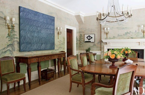 "A Cy Twombly ""Blackboard"" painting and a small geometric Franz Kline play off the hand-painted Gracie scenic wallpaper in the dining room; surrounding the late-Georgian dining table is a suite of Empire chairs."