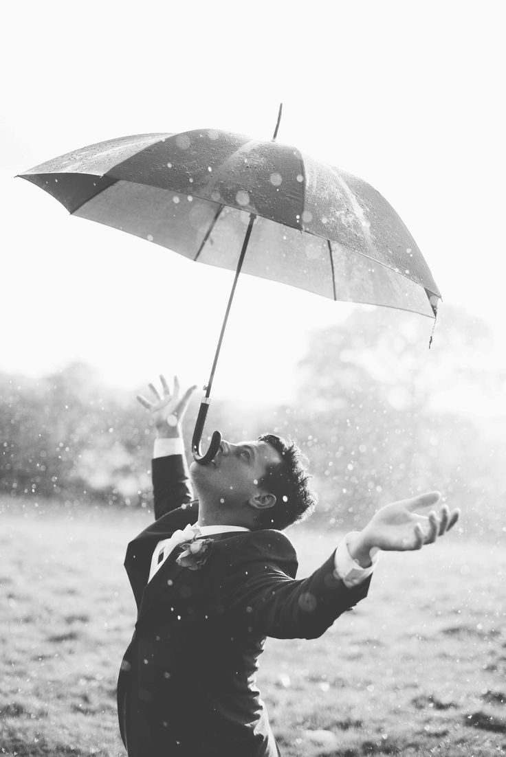 a best man balancing an umbrella on his nose during a wet wedding