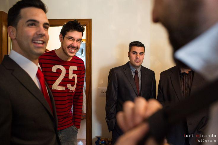 Novio preparándose para vestirse el día de su boda acompañado de sus amigos