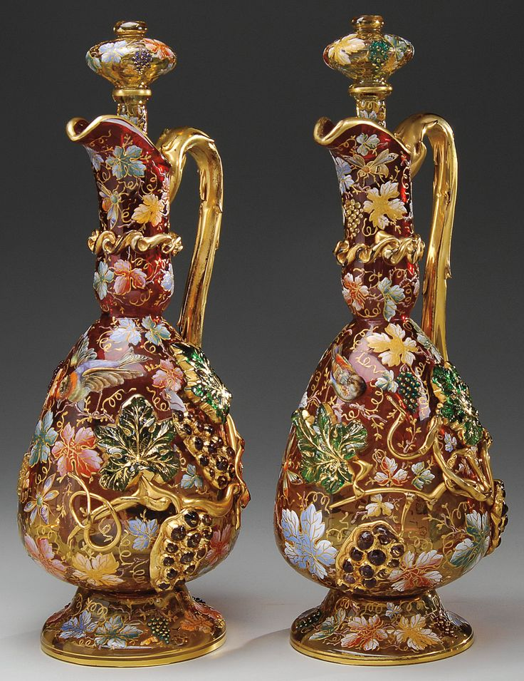A pair of Moser decorated decanters with heavy applied grape leaves, stems, and clusters against a shaded Amberina background.