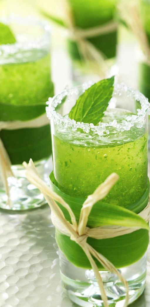 Mini mint mojitos in a tall shot glass, wrapped with a leaf and raffia.