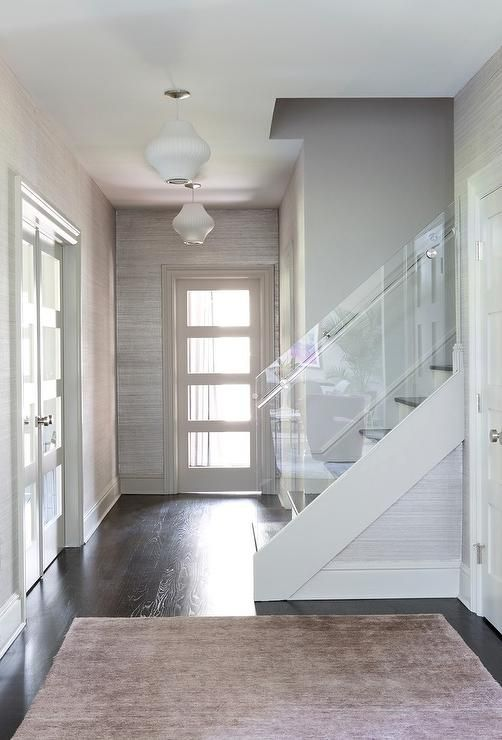 Welcoming white and gray contemporary foyer is clad in gray grasscloth wallpaper illuminated by white modern light pendants and features a gray rug placed on a dark stained oak wood floor in front of a staircase fitted with an acrylic railing.