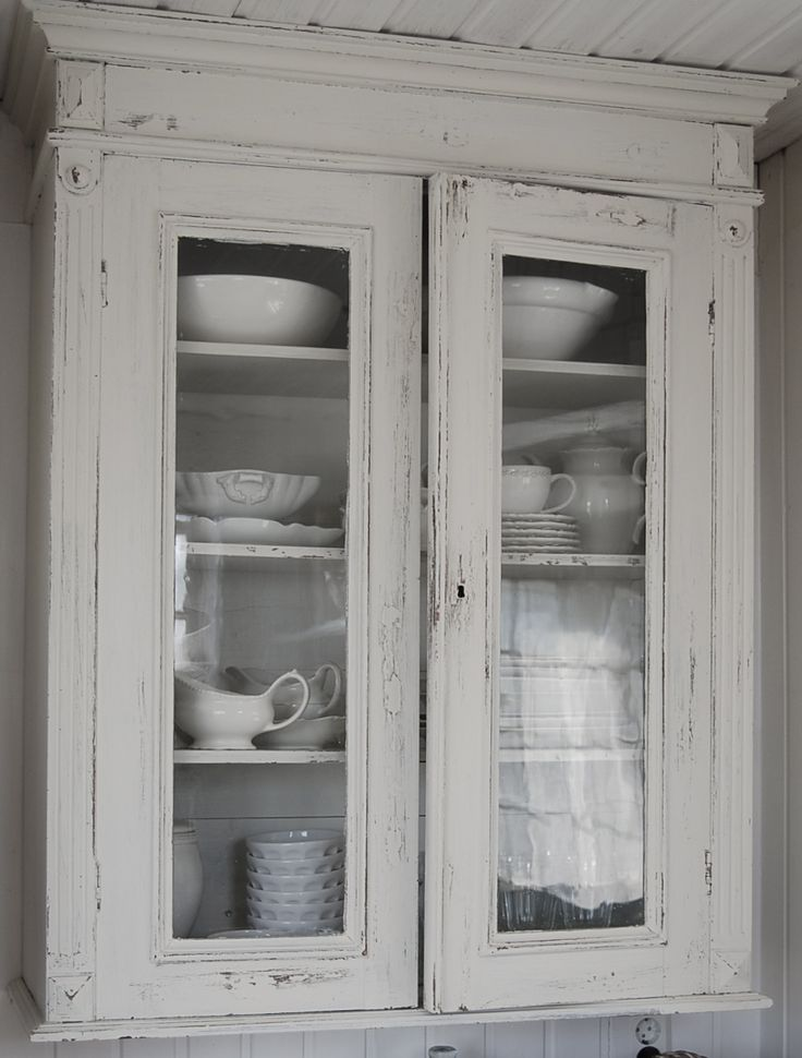 White Vintage Wall Cabinet - what a great old cabinet, with glass panels and lots of shelves for displaying collected ironstone - via Hvitur Lakkris